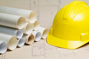 Hard hat and rolls of construction blueprints